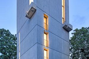 Rechts: An dem Licht, das abends durch die bis zu 7,5 m hohen Fensterschlitze dringt, ist deutlich zu erkennen, dass der Beton-Kirchturm in Freiburg im Breisgau eine neue Nutzung bekommen hat⇥Foto: Martin Baitinger / Focus
