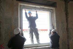 Mit vereinten Kräften werden die großen Fensterrahmen in die offene Laibung eingesetztFotos: Kneer-Süd-fenster