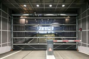 """Links: Die Tiefgarage wird von der Neubrückstraße aus über ein Hörmann Aluminium-Rahmentor """"ALR F42"""" erschlossen. Dieses fügt sich unauffällig in die Gesamtgestaltung ein"""
