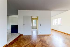 Wohnraum im Erdgeschoss mit aufgearbeitetem Fischgrätparkett und grau gestrichener Decke