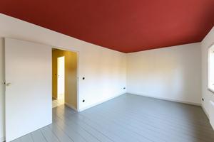 Schlafzimmer im Obergeschoss mit hellgrün lackiertem Dielenboden und rot gestrichener Decke