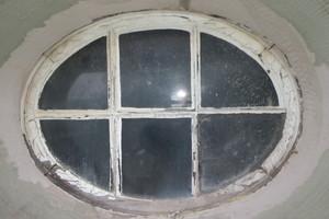 Ein Ochsenaugenfenster vor der Sanierung