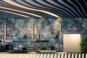 Über der Bar des Sushi-Restaurants Fuji Yama hängen goldfarbene Zylinder-Pendelleuchten, dahinter an der Wand eine Tapete mit abstrahiertem Kirschblütenmuster