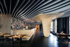 """Der Filz der dunklen Akustikbaffeln an der Decke besteht aus recycelten PET-Flaschen. An einer der massiven Stützen """"fließen"""" die hellen Holzlamellen im Raum in einer Tropfenskulptur als Stalaktit von der Decke herunter<br />"""