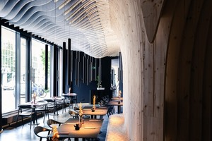 Die Scheiben bilden eine fließende Wellenstruktur, die sich von der Decke über die Wände zieht und vom Boden wieder als Sitzmöbel emporhebt