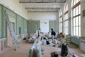 Die Geometrien der historischen Holztäfelung an den Wänden des Examensaals wurden in einer abstrahierten Ausführung eingebaut<br />