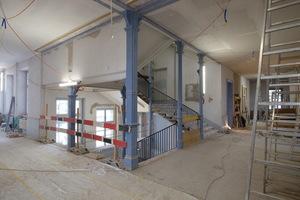 Durch die Umplatzierung des Lifts aus dem Treppenauge in einen Seitenbereich kommen die markanten Gusseisenstützen im Treppenhaus wieder zur Geltung