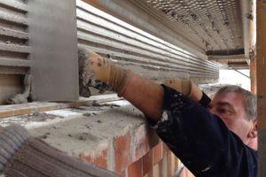 In den grau durchgefärbten Modellieroberputz arbeiten die Handwerker die Kammstruktur mit einer Reliefierung von 15 / 15 mm ein