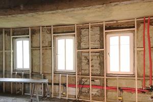 Holzkonstruktion vor dem bestehenden Fachwerk, das anschließend mit Schilfrohrmatten versehen wird. Die Matten dienen als Träger für den folgenden Lehmputz