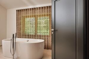 Im Bad bilden die schwarzen Türen einen Kontrast zu den hellen Wänden und der Wanne