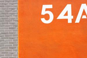 Farbig beschichtete Sichtbetonflächen mit Hausnummern gliedern die Klinkerfassaden und geben Orientierung