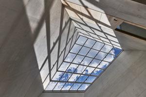 Ein großes Oberlicht in der geneigten Dachfläche überspannt wie schwebend die atriumartige Halle