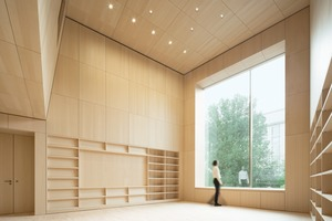 Das große Fenster in der Westfassade der mit Holz verkleideten Bibliothek öffnet den Blick auf den Vorplatz