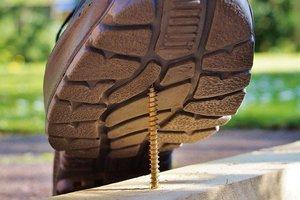 Auf Baustellen lauern viele Gefahren, wie beispielsweise ein hoch stehender Nagel. Alleinarbeiter müssen besonders geschützt  werden.