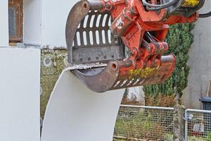 Rechts: Die Putzstreifen werden ähnlich wie eine Tapete mit dem Greifer eines Baggers vom Dämmstoff abgezogen