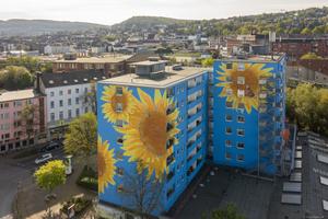 An der Hausfassade eines Hochhauses in Wuppertal blühen überdimensionale Sonnenblumen auf blauem Grund