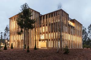 Die Baumstammfassade hat statisch keinerlei Funktion, zeigt aber bereits von weitem an, worum es hier geht: Holz