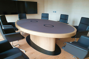 Der große Tisch im Konferenzraum hat eine Linoleumplatte mit zwei Klappen unter denen sich Steckdosen und Laptopanschlüsse befinden