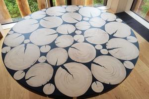 Für die Tische der Mitarbeiterkantine wurden auf eine Trägerplatte Baumscheiben unterschiedlicher Durchmesser angeordnet und mit dem Harz vergossen