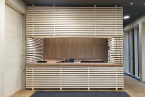 Der Schreibtisch im Chefzimmer und die Kaffeestationen erinnern in ihrer Gestaltung an Holzstapel, wie man sie in vielen Bereichen im Sägewerk findet