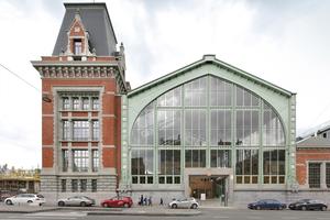 Außenansicht einer der Seitenhallen des historischen Güterbahnhofs Gare Maritime in Brüssel. Was man von außen nur durch das Eingangsportal hindurch erahnen kann: Im Gebäude stehen heute keine Züge mehr, sondern moderne Holzbauten