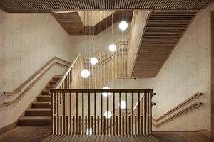 Blick in eines der Treppenhäuser nach Fertigstellung. Die Holzoberflächen an den Wänden sind sichtbar geblieben