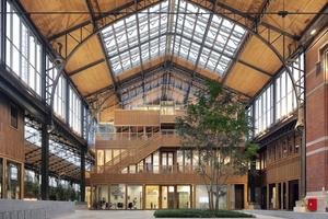 Blick in eine der restaurierten und sanierten Hallen des ehemaligen Güterbahnhofs Gare Maritime in Brüssel nachdem der Einbau der Holzbauten abgeschlossen war