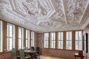 """Die """"Große Stube"""" ist ein repräsentativer Raum. Sie ist kunstvoll mit Seidentapete ausgekleidet und von einer reich verzierten Stuckdecke überspannt"""