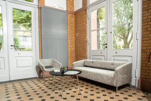 Mehr Wohnlichkeit erhält die großzügige ehemalige Eingangshalle durch hochwertige Loungemöbel der Dauphin-Marke Züco: Averio-Sessel und Destino-Sofa in zurückhaltendem Grau gliedern sich harmonisch in das Ambiente ein.