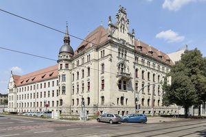Zur Straße hin sind große Teile der Hauptfassaden des Landgerichts Magdeburg mit Naturstein verkleidet