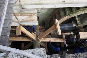 Der Einbau des neuen Rads beginnt mit dem Einsetzen und Fixieren der drei Speichen in den Wellbaum. Dann werden die Kopfhölzer aufgesetzt, in die Waage gesetzt, ausgerichtet und fixiert