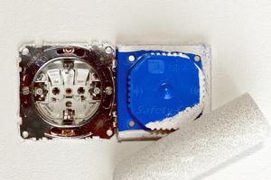 """Zur Hälfte mit einer """"Safety-Cap"""" abgedeckte Doppelsteckdose. Die Form der """"Safety-Cap"""" ist auf den Radius der gängigen Farbwalzen abgestimmt. So entsteht beim direkten Anrollen keine Farbabschattung"""