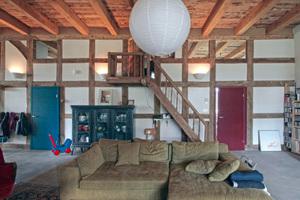 Wohnzimmer mit alter Holztreppe im Hintergrund, die zur Zwischenebene hinauf führt<br />