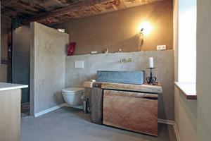 Elternbad mit Waschtisch aus Altholz und einem aus Terrazzobeton gegossenen Waschbecken darauf