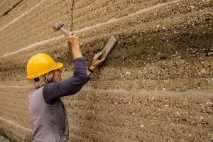 Die Fugen zwischen den Wandtafeln werden mit Lehm verschlossen und mit einem Brett und Fäustel verdichtet und geglättet