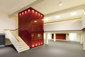 Mit roten Glasplatten verkleideter Aufzugsschacht