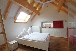 """Das Schlafzimmer wird im Dachgeschoss überwiegend durch ein großes quer liegendes Dachfenster belichtet. Ein schmales quer liegendes Fenster in der Giebelwand lässt zusätzlich Tageslicht herein<span class=""""bildnachweis"""">Fotos: Thomas Wieckhorst</span>"""