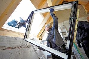 Der Rahmen für das große, quer liegende Dachfenster wird zur Montage gebracht