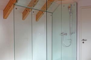 Die Dusche stellten die Glaser im Schlafzimmer als Stahl-Glas-Konstruktion auf Edelstahlfüßen lose im Dachgeschoss auf