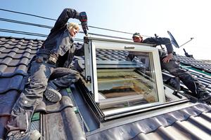 """Einbau des großen quer liegenden Dachfensters in der Dachfläche aus schwarz engobierten Ziegeln<span class=""""bildnachweis"""">Fotos (4): Lars Behrendt</span>"""