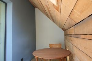 Überdachter Sitzplatz im Obergeschoss im Raum zwischen der alten Hülle und dem neuen Passivhaus<br />