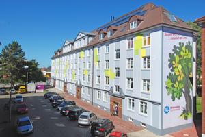 Die Gestaltung der Fassade eines Wohngebäudes in der Cuxhavener Rathausstraße ist ein schöner Blickfang. Die Giebelseite ziert ein stilisierter Kastanienbaum