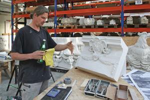 Bildhauermeister Andreas Klein neben einem kleinen Modell, das er von einer Wappenkartusche angefertigt hat<br />