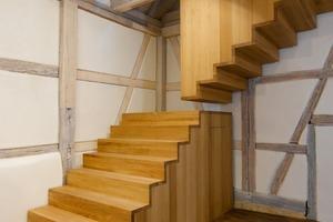 Rechts: Das Dachgeschoss wird über eine Treppenskulptur aus Eichenbohlen erschlossen<br />