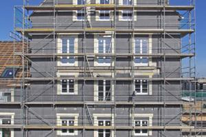 Auf der Baustelle stehen die Brandschutzriegel als helle Flächen im Kontrast zum dunklen WDVS von Renowall