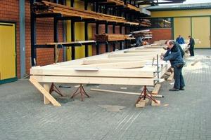 Oben: Die beiden 3m hohen Greimbinder fertigten die Zimmerleute in der Werkstatt in Lohne vor<br />Daneben: Auch die 9m hohen Holztafelwände wurden in der Werkstatt inklusive Putz und Anstrich vorgefertigt