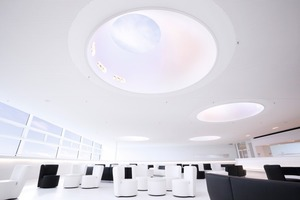 """Die Skylobby über dem Theatersaal. Die Lochplattendecke wird von kegelförmigen Öffnungen, so genannten """"Lichtkanonen"""", durchdrungen, über die zusätzliches Tageslicht von oben in die Skylobby gelangt<br />"""