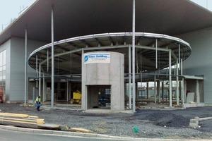 Die Strahlrohr- und Strahlträgerkonstruktion nimmt die elliptische Formgebung des Showrooms unter dem Dach des Hauptgebäudes vorweg<br />