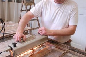 Hier wird der Kitt mit Hilfe eines Wärmestrahlers abgelöst, um die Einfachverglasung aus einem alten Holzfenster entfernen zu können<br />