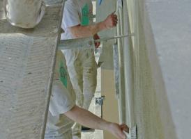 """<div class=""""99 Bildunterschrift_negativ"""">Nachdem der Kalk-Zement-Schlämmputz getrocknet ist, bearbeiten ihn die Handwerker mit Bürsten, um Arbeitsspuren der Kelle auszugleichen</div>"""